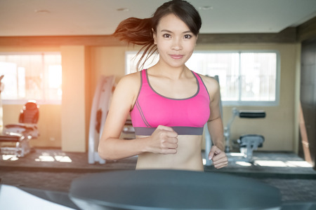 smile close up: woman run on treadmill in the gym Stock Photo