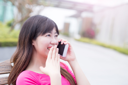 woman talk on phone happily in the park