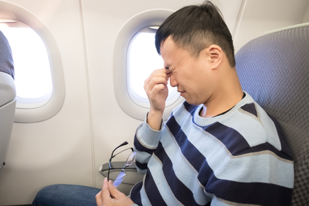 man feel eye pain in the airplane Stock Photo