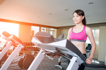 close up: woman smile happily and stand on treadmill in the gym Stock Photo