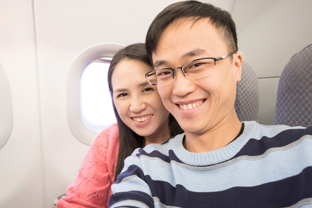 couple selfie and smile happily in airplane photo