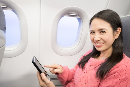 Middle aged woman smie and use phone in the airplane photo