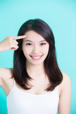 beauty skincare woman smile happily and touch her forehead on green background Stock Photo