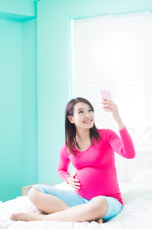 beauty pregnancy woman selfie and smile happily on the bed Stock Photo