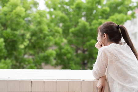 balcony: woman feel depression and look somewhere next to the balcony