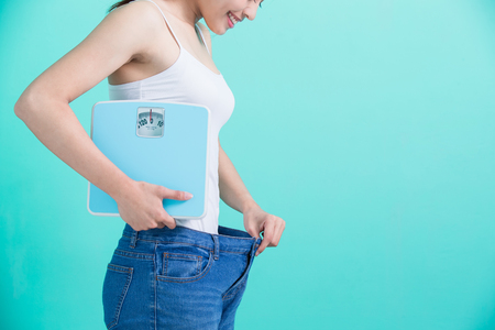 beauty woman with slim waist on the green background Stock Photo