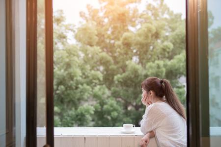 Kobieta czuje depresję i patrzy gdzieś obok balkonu