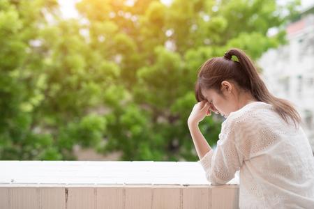 여자는 우울증을 느끼고 발코니 옆에있다.