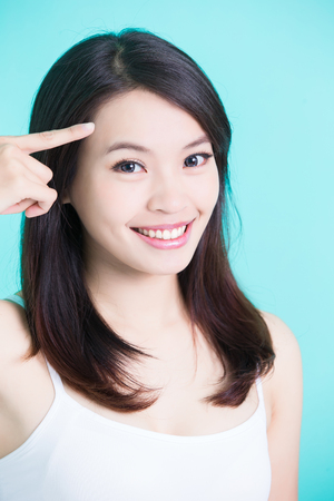 beauty skincare woman smile happily and touch her forehead on green background Banco de Imagens