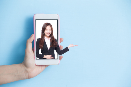 hand take smart phone with businesswoman show something in screen on blue background