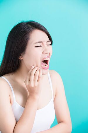 beauty woman feel pain with toothache on the green background