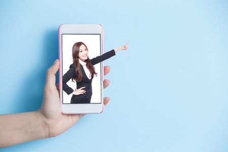 hand take smart phone with businesswoman show something in screen on blue background Stock Photo