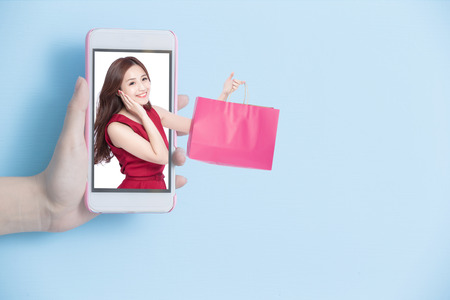 hand take smart phone with woman hold shopping bag in screen on blue background photo