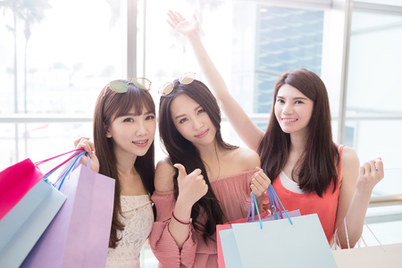 consumerism: beauty women take shopping bag and thumb up in mall