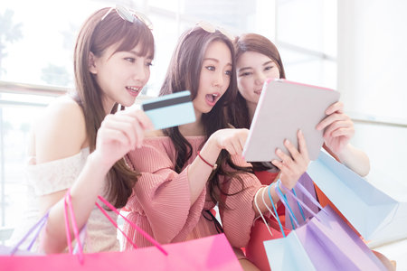 screen: women take credit card and tablet pc in the shopping mall