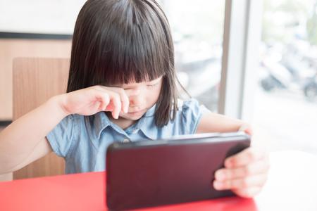 Schattig meisje gebruik telefoon en voel oogpijn in de resturant
