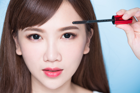 make a paste: beauty woman take mascara on the blue background Stock Photo