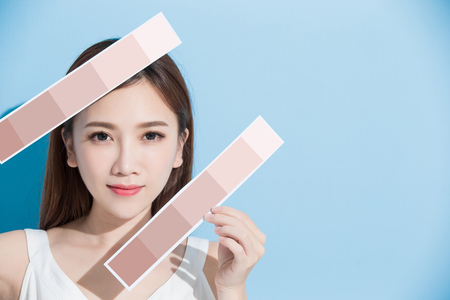 woman take skin color scale on the blue background 스톡 콘텐츠