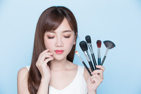 make a paste: beauty woman take makeup brush on the blue background