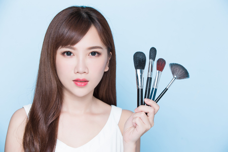 beauty woman take makeup brush on the blue background
