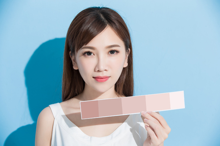 woman take skin color scale on the blue background Stock Photo