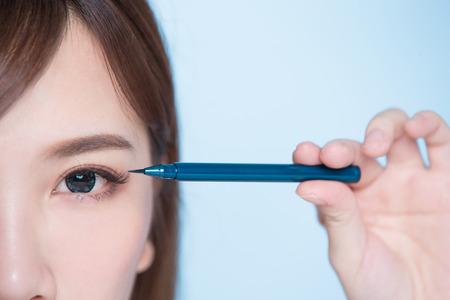 beauty woman woman take eyeliner on the blue background 版權商用圖片 - 80868625