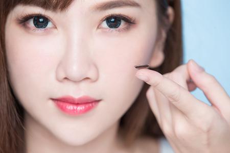 女性は、青の背景にコンタクト レンズを取る