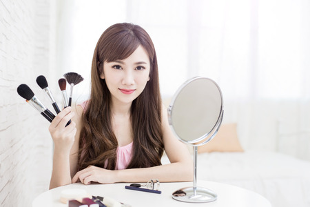 make a paste: beauty woman take makeup brush on the bed room