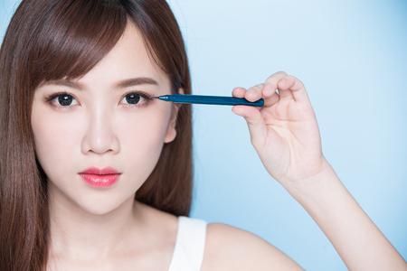 Mujer de belleza mujer tomar eyeliner sobre el fondo azul Foto de archivo