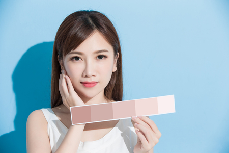 woman take skin color scale on the blue background 写真素材