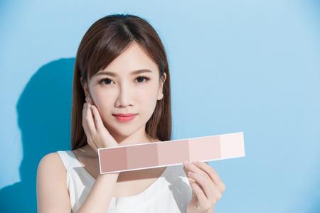Frau nehmen Haut Farbe Skala auf dem blauen Hintergrund Standard-Bild - 80868118