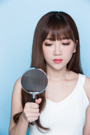 beauty woman take magnifying check her hair on the blue background