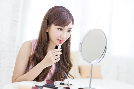 beauty woman use lipstick and look mirror in the room Stock fotó
