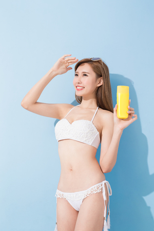woman take sunscreen on the blue background