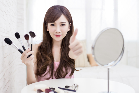 face to face: beauty woman take makeup brush on the bed room