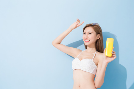 face to face: woman take sunscreen on the blue background
