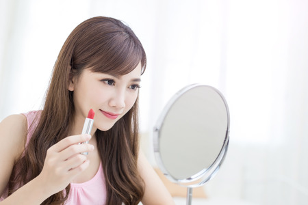 woman mirror: beauty woman use lipstick and look mirror in the room Stock Photo