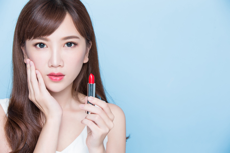 beauty woman take lipstick and touch her face on the blue background Stock Photo