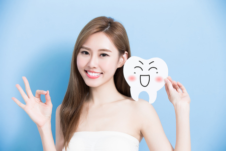 whiten: woman take cute tooth and show ok to you on blue background