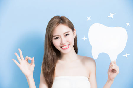introduce: woman take cute tooth and show ok to you on blue background