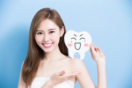 happy people: woman take cute tooth and show something to you on blue background
