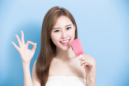 woman take popsicle and show ok to you on the blue background
