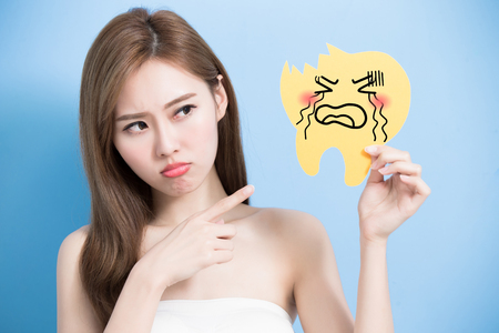 woman take decay tooth billboard and feel angry on the blue background Stock Photo