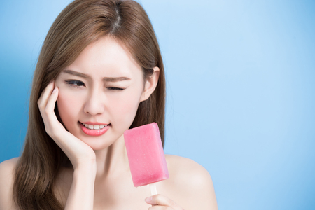 woman take popsicle and feel upset with sensitive problem on the blue bakcground Stockfoto