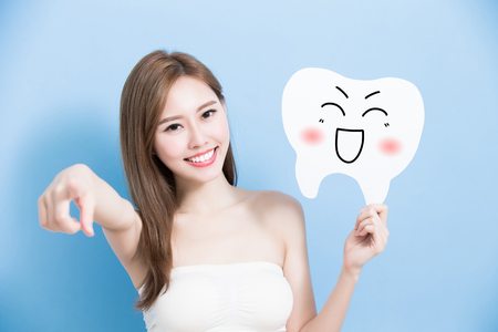 woman take cute tooth and introduce on blue background