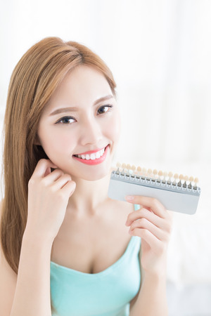 woman with tooth color palette at home Stock Photo
