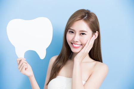 여자는 귀여운 치아 광고판을 가지고 파란색 배경에 그녀의 얼굴을 만진다.
