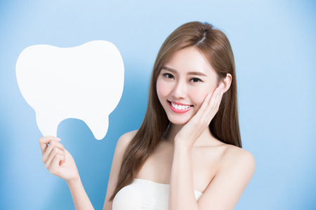 woman take cute tooth billboard  and touch her face on the blue background 版權商用圖片