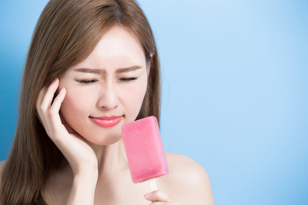 woman take lolly and feel upset with sensitive problem on the blue bakcground Stockfoto