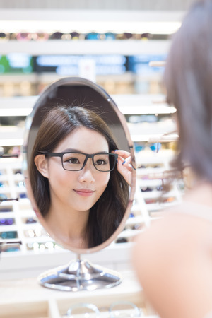 woman mirror: beauty woman wear eyeglasses in the store